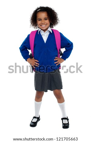 Primary school girl posing confidently with hands on her waist, carrying pink school bag. - stock photo
