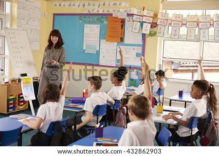 Primary school kids raising hands in class to answer teacher - stock photo