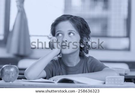Primary schoolboy at his desk. - stock photo