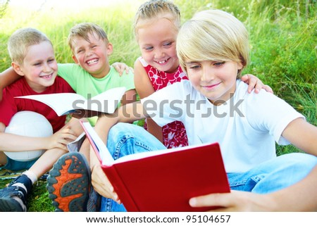 primary schoolchildren enjoying reading the same book, in the late afternoon sunshine - stock photo