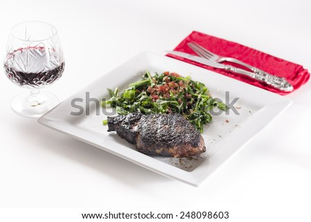 Prime rib eye steak served with wine and spinach sauteed in olive oil with garlic and bacon bits - stock photo