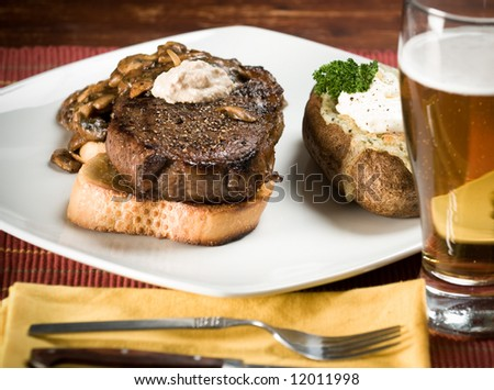 Prime Rib steak on garlic toast, with Blue Cheese and rosemary stuffed potato, mushrooms in balsamic vinegar reduction, with horseradish sauce and beer. - stock photo