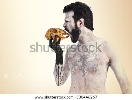 Primitive man eating a rabbit skull - stock photo