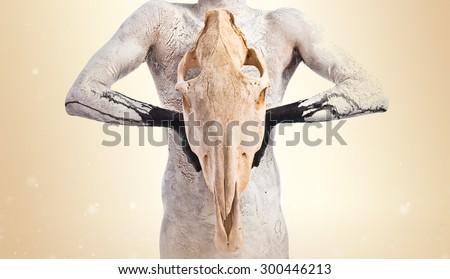 Primitive man holding horse skull - stock photo