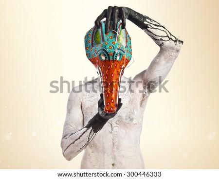 primitive man with fox mask over ocher background - stock photo