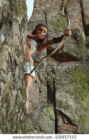 Primitive woman standing on a rock and holding a bow. Amazon woman - stock photo