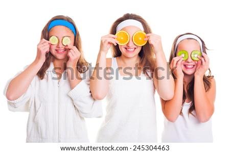 Primping teenager girls having fun with fruit slices - stock photo