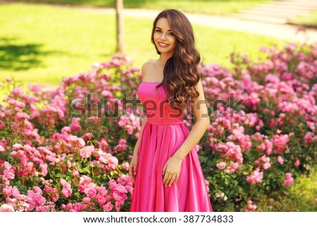 Princess. Young beautiful pretty woman posing in long evening luxury dress against bushes with pink roses on a sunny summer day. Vogue style fashion sensual portrait - stock photo