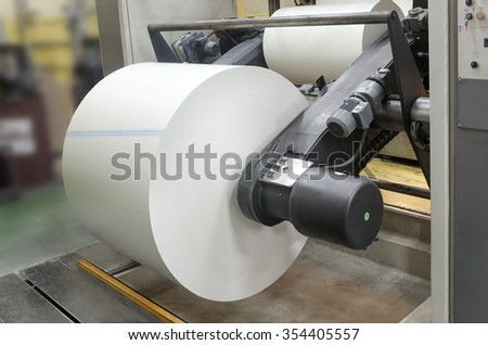 Print machine roll in newspaper offset print production line wide shot - stock photo