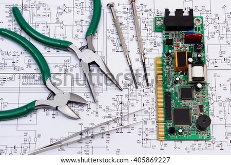 Printed circuit board with electrical components and precision tools lying on construction drawing of electronics, drawings and precision tools for engineer jobs, technology - stock photo