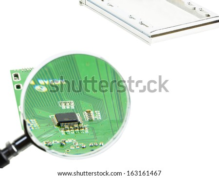 Printed circuit board with magnifying glass - stock photo