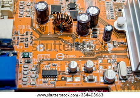 Printed orange computer motherboard with microcircuit - stock photo