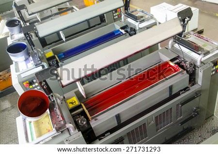 printing machine cylinders and printing ink pot - stock photo