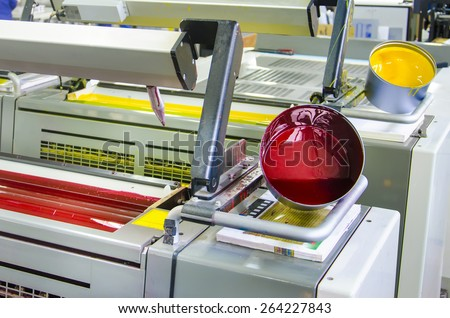 printing machine cylinders and printing ink pot with red yellow color - stock photo