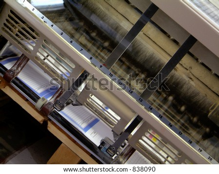 Printing machine in action in printers shop - stock photo