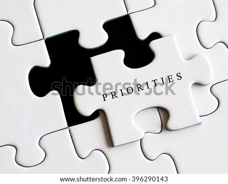 Priorities written on missing puzzle. - stock photo