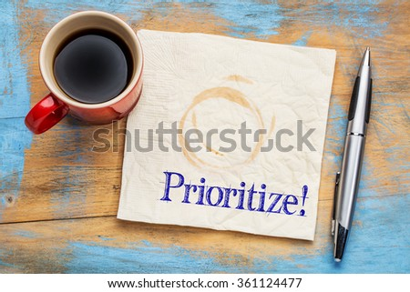prioritize - reminder or productivity concept on a napkin with a cup of coffee - stock photo