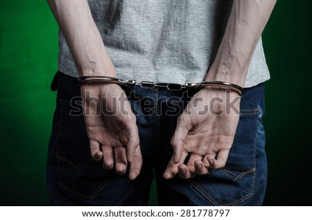 Prison and convicted topic: man with handcuffs on his hands in a gray T-shirt and blue jeans on a dark green background in the studio, put handcuffs on the drug dealer, the view from the back - stock photo
