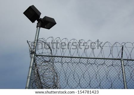 Prison barbed wire fence  - stock photo