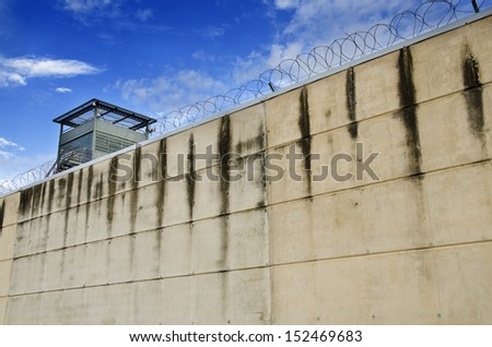 Prison wall and cloudy sky. - stock photo