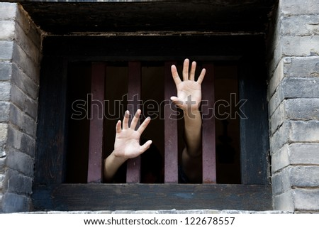 Prisoner hands stretch out from prison bars - stock photo