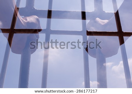 Prisoner holding bars in the jail. Double exposure - stock photo