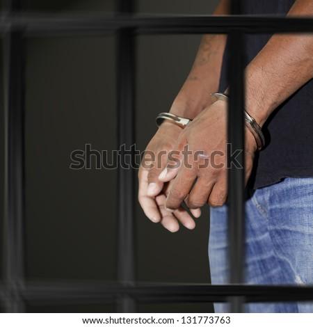 Prisoner locked in handcuffs in prison on black background - stock photo