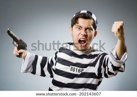 Prisoner with gun against dark background - stock photo