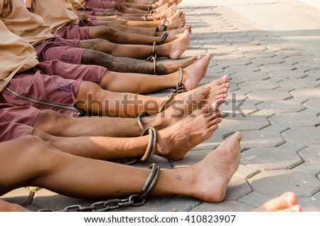Prisoners are bound with chains . To prevent the escape of the journey to find justice in court. (Tattoo on leg Be made between stints in prison. Thailand Which is considered a a serious offense) - stock photo
