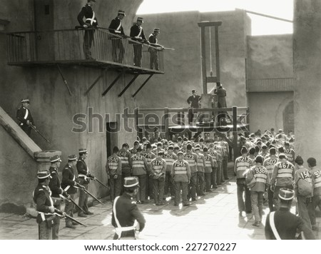 Prisoners prepare for execution by guillotine - stock photo