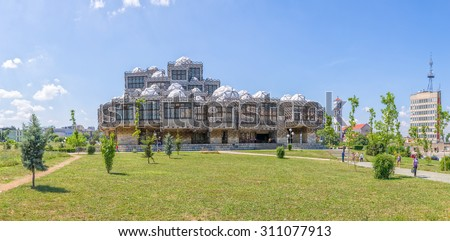 PRISTINA, KOSOVO - JULY 01, 2015: People walking in the park by the famous building of the National library of Kosovo designed by architect Andrija Mutnjakovic. - stock photo