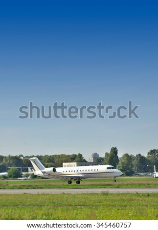 Private business jet landing at the airport on a sunny summer day - stock photo