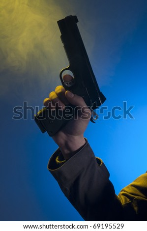 Private detective holding a gun, shooted in studio on a blue background with yellow light and smoke - stock photo