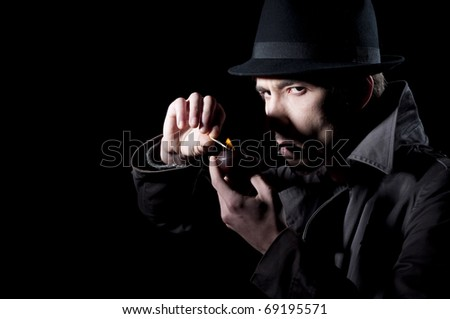 Private detective lighting his pipe, isolated on a black background - stock photo