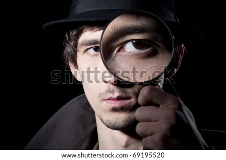 Private detective watching through a magnifying glass, isolated on a black background - stock photo