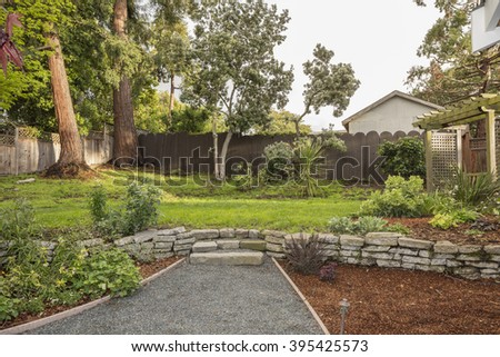 Private green yard with new created path / walk way and unique wooden swing with large grown trees. - stock photo