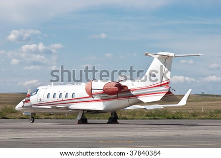 Private jet airplane parked on airfield runway with covered engines and blue sky with clouds - stock photo