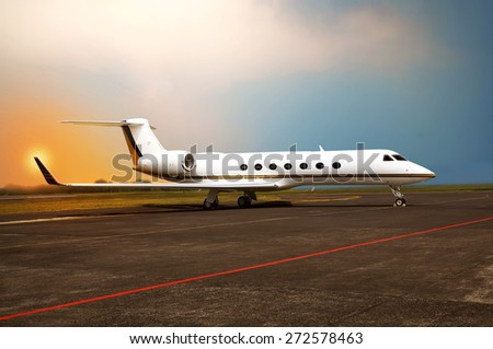 Private jet airplane parking at the airport. With sunset background - stock photo