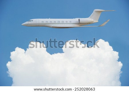 Private jet airplane with fluffy clouds - stock photo