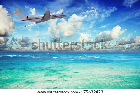 Private jet over the tropical sea - stock photo