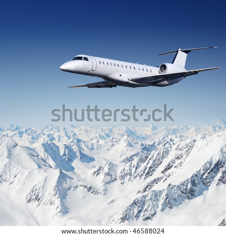 Private jet plane flying over mountains - stock photo