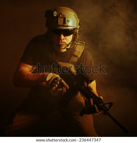 Private military contractor PMC with assault rifle on dark background - stock photo