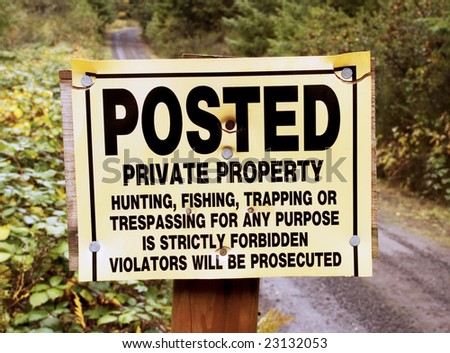 private no trespass sign in front of country road - stock photo