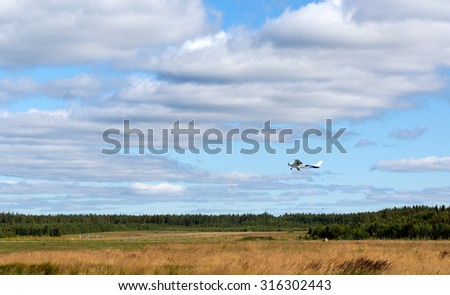 Private propeller aircraft on take-off on the background of clouds - stock photo