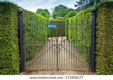 Private sign attached to an ornate wrought iron gate leading int - stock photo