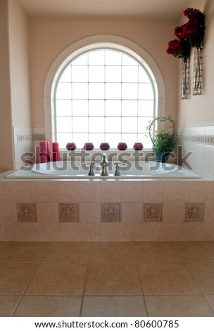 Private whirlpool bath below an arched, glass block window. - stock photo