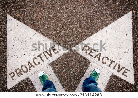 Proactive and reactive dilemma concept with man legs from above standing on signs - stock photo