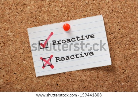 Proactive and Reactive tick boxes on a paper note pinned to a cork notice board. - stock photo