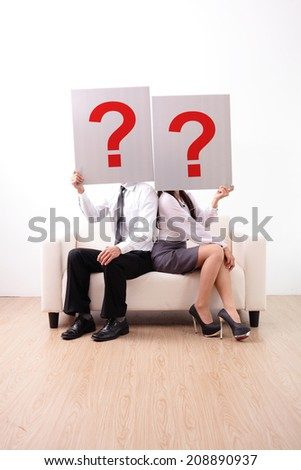 Problem in young couple - young couple holding billboard sign with question mark - stock photo