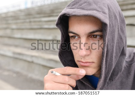 problem of adolescence.Sad and thinker teenager smoking cigarette in urban setting - stock photo
